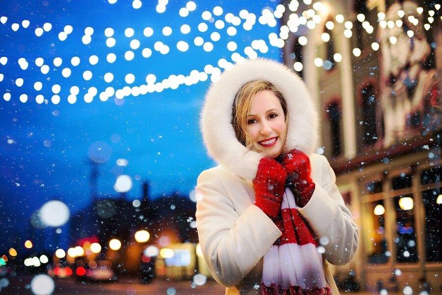 Vesela gospa v novoletno okrašenem mestu