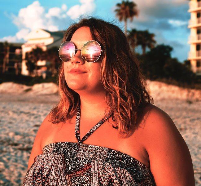 Ženska s sončnimi očali gleda sončni zahod