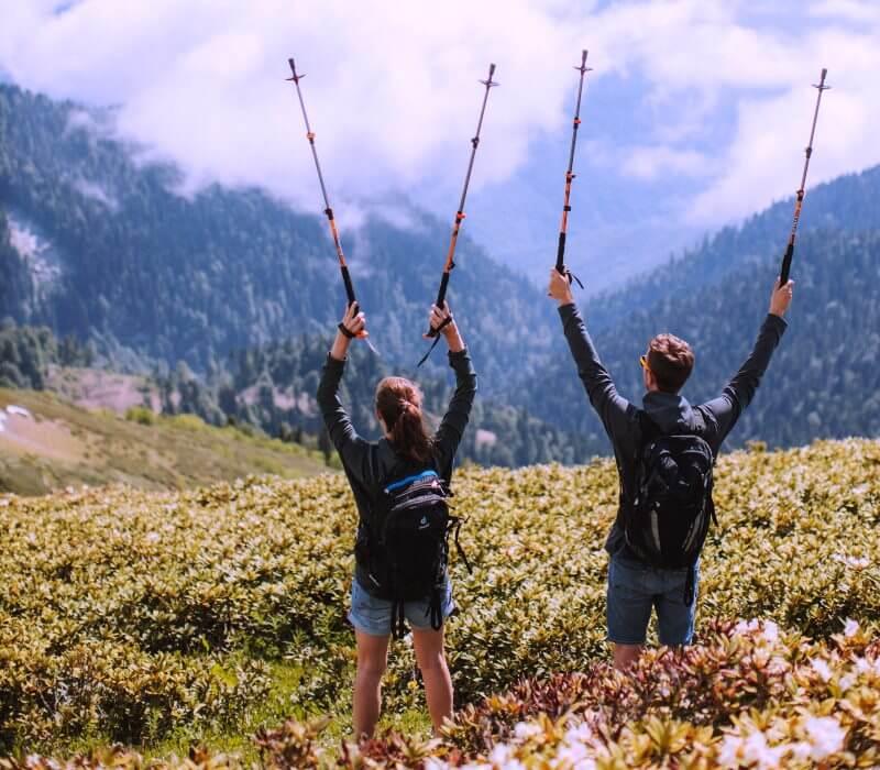 Zmagovalni Občutek - Par v hribih z dvignjenimi palicami